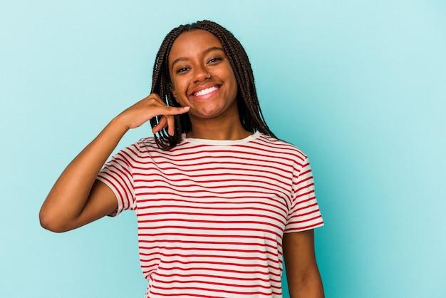 Młoda kobieta african american na białym tle na niebieskim tle pokazując gest połączenia z telefonu komórkowego palcami.