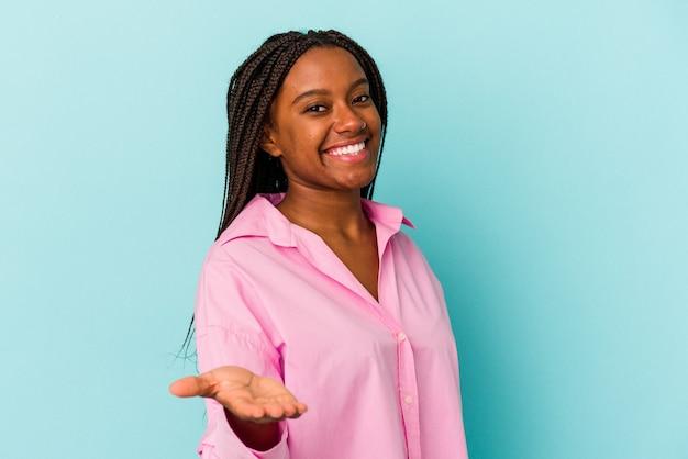 Młoda kobieta african american na białym tle na niebieskim tle, rozciągając rękę na aparat w geście pozdrowienia.