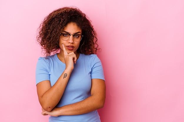 Młoda kobieta african american na białym tle na różowym tle patrząc z boku z wyrazem wątpliwości i sceptyczny.