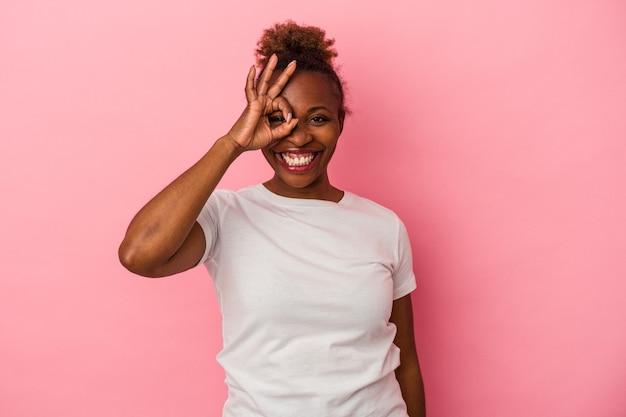 Młoda kobieta african american na białym tle na różowym tle podekscytowany, trzymając ok gest na oko.