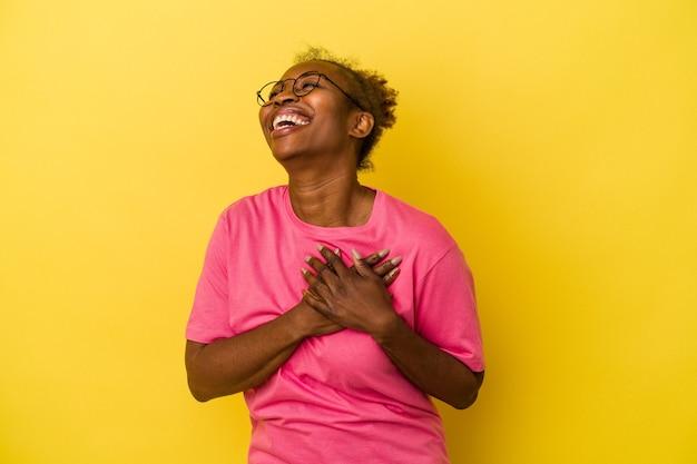 Młoda kobieta african american na białym tle na żółtym tle śmiejąc się trzymając ręce na sercu, pojęcie szczęścia.
