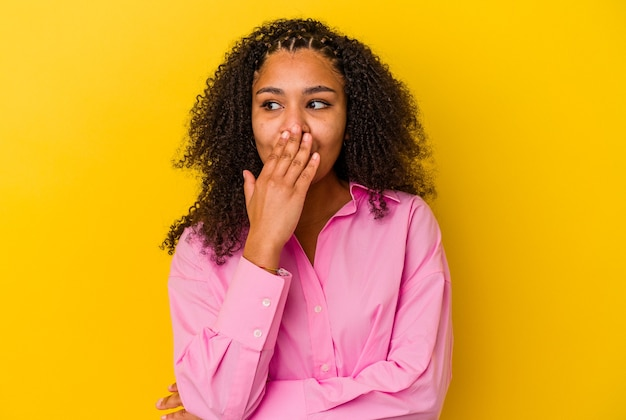 Młoda kobieta african american na białym tle na żółtym tle ziewanie pokazując zmęczony gest zasłaniając usta ręką.