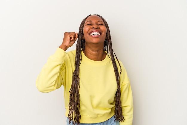 Młoda kobieta african american na białym tle świętuje zwycięstwo, pasję i entuzjazm, szczęśliwy wyraz.