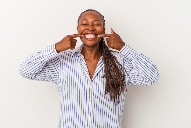 Młoda kobieta african american na białym tle uśmiecha się, wskazując palcami na ustach.
