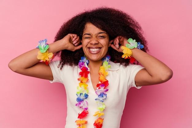 Młoda kobieta african american sobie hawajskie rzeczy obejmujące uszy rękami.