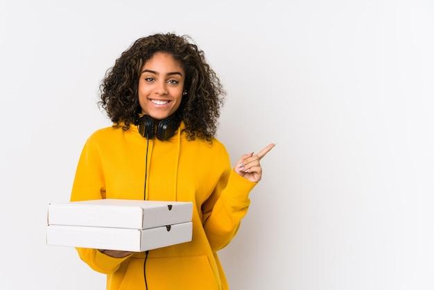 Młoda kobieta african american student trzymając pizze, uśmiechając się i wskazując na bok, pokazując coś w pustym miejscu.