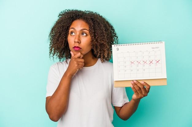 Młoda kobieta african american, trzymając kalendarz na białym tle na niebieskim tle, patrząc w bok z wyrazem wątpliwości i sceptyczny.