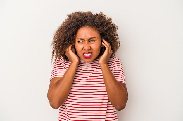 Młoda kobieta african american z kręconymi włosami na białym tle na białym tle obejmujące uszy rękami.