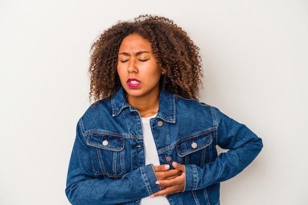 Młoda kobieta african american z kręconymi włosami na białym tle o ból wątroby, ból brzucha.