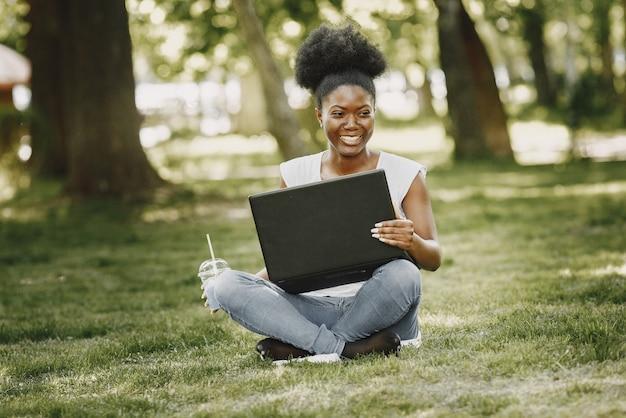 Młoda kobieta afro-amerykańska patrząca w laptopie na park