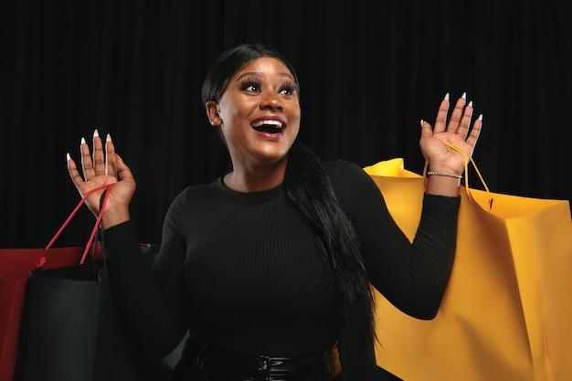 Młoda kobieta afro-amerykańska zakupy z kolorowymi paczkami na czarnej ścianie.