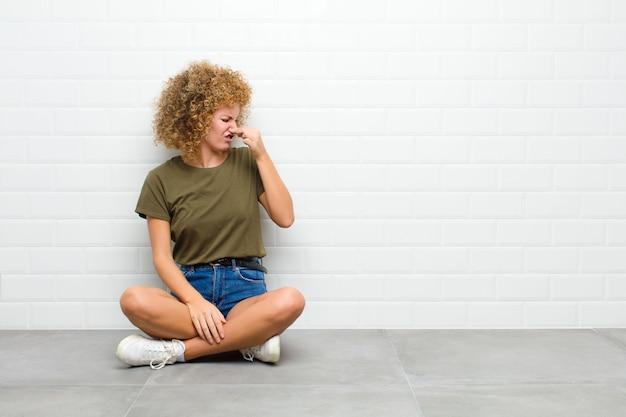 Młoda kobieta afro czująca się zniesmaczona, trzymająca nos, aby uniknąć wąchania nieprzyjemnego i nieprzyjemnego smrodu na podłodze