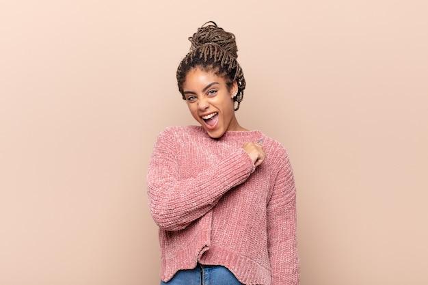 Młoda kobieta afro czuje się szczęśliwa i uśmiecha się niedbale, patrząc na przedmiot lub koncepcję trzymaną w dłoni na boku