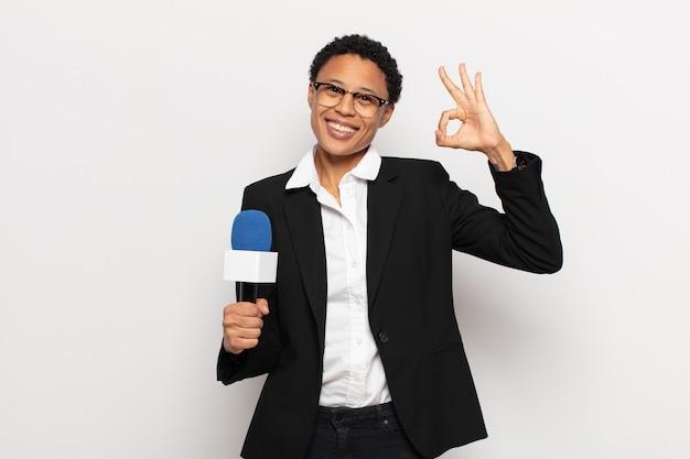 Młoda kobieta afro czuje się szczęśliwa, zrelaksowana i usatysfakcjonowana, okazując aprobatę dobrym gestem, uśmiechając się