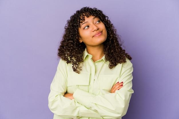 Młoda kobieta afro na białym tle marzy o osiągnięciu celów i zamierzeń