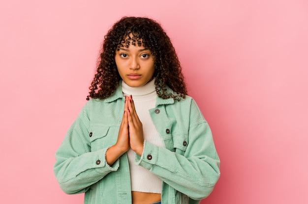 Młoda kobieta afro na białym tle modląc się, okazując oddanie, osoba religijna szukająca boskiej inspiracji