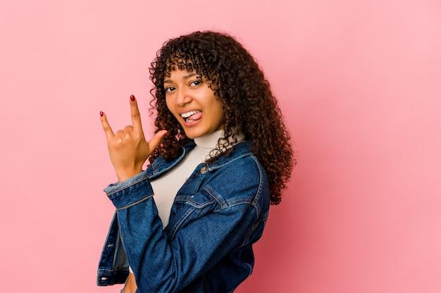 Młoda kobieta afro na białym tle pokazuje rockowy gest palcami