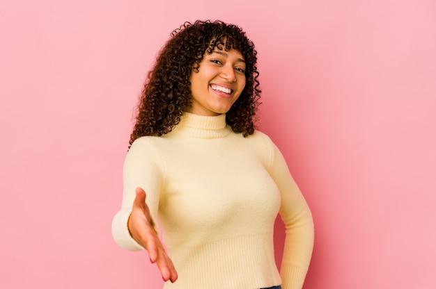 Młoda kobieta afro na białym tle rozciąganie ręki w aparacie w geście pozdrowienia