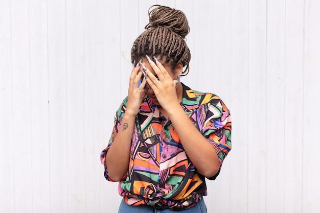 Młoda kobieta afro obejmujące oczy rękami z smutnym na białym tle