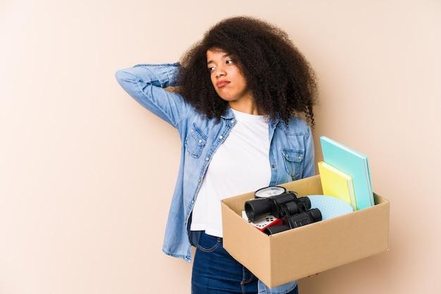 Młoda kobieta afro przeprowadzka do domu odizolowana młoda kobieta afro dotykając tyłu głowy, myśląc i dokonując wyboru.