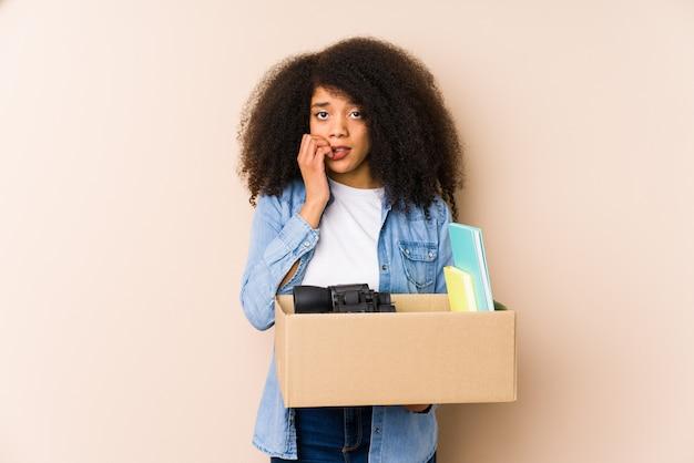 Młoda kobieta afro przeprowadzka do domu odizolowana młoda kobieta afro obgryzanie paznokci, nerwowa i bardzo niespokojna.