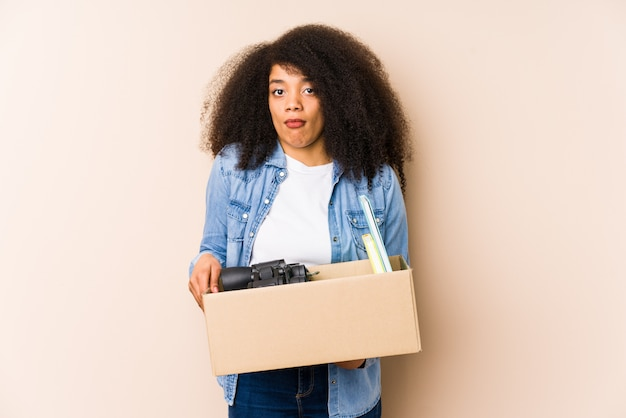 Młoda kobieta afro przeprowadzka do domu odizolowana młoda kobieta afro wzrusza ramionami i myli oczy otwarte.