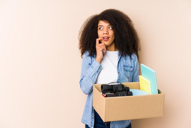 Młoda kobieta afro przeprowadzka do domu odizolowana młoda kobieta afro zrelaksowana, myśląc o czymś, patrząc na miejsce.