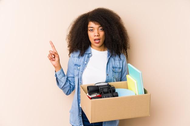 Młoda kobieta afro przeprowadzka do domu odizolowane młoda kobieta afro o pomysł, koncepcja inspiracji.