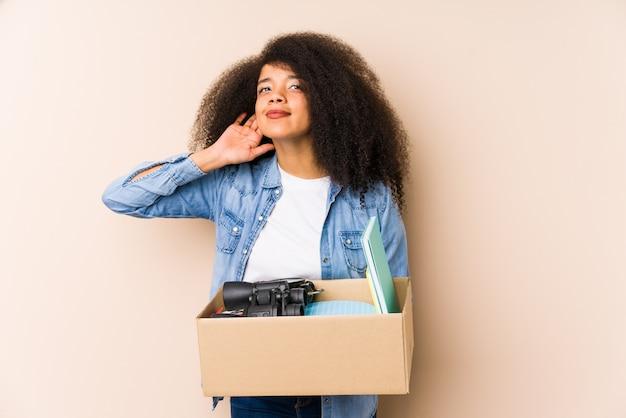 Młoda kobieta afro przeprowadzki do domu izolowane młoda kobieta afro próbuje słuchać plotek.