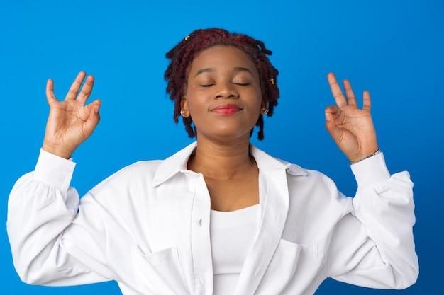 Młoda kobieta afro relaksuje się z zamkniętymi oczami na niebieskiej powierzchni