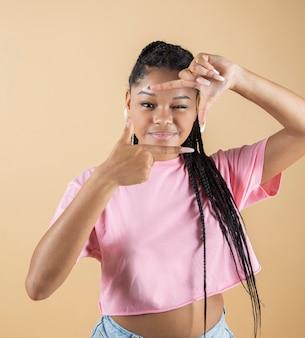 Młoda kobieta afro robi gest fotograficzny w studio