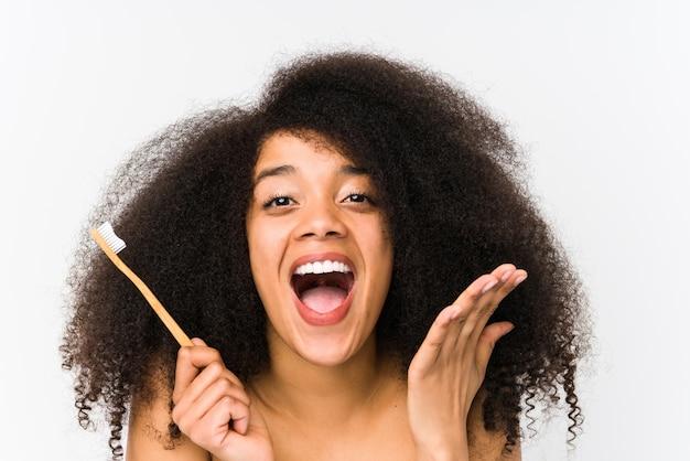 Młoda kobieta afro trzyma szczotkę do zębów świętuje zwycięstwo