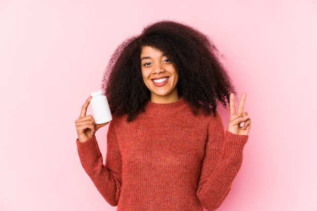 Młoda kobieta afro trzyma witaminy odizolowanych młoda kobieta afro trzyma witaminy pokazywanie palcami numer dwa.