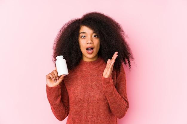 Młoda kobieta afro trzyma witaminy odizolowanych młoda kobieta afro trzyma witaminy zaskoczony i zszokowany.
