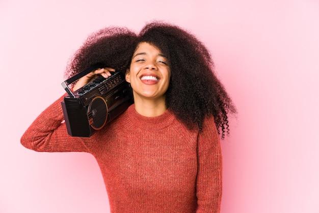 Młoda kobieta afro trzymając kasetę na białym tle śmiechu i zabawy.