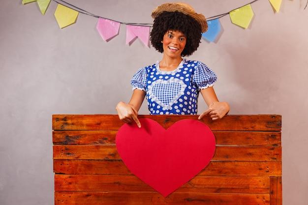 Młoda kobieta afro ubrana na imprezę junina za drewnianą deską z sercem