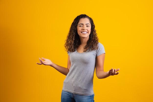 Młoda kobieta afro uśmiecha się na żółtym tle z wolnego miejsca na tekst. młody student