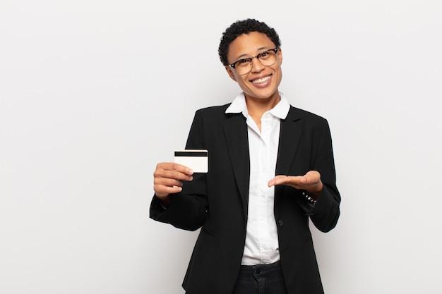 Młoda kobieta afro uśmiecha się radośnie, czuje się szczęśliwy i pokazuje koncepcję w przestrzeni kopii z dłoni