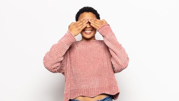 Młoda kobieta afro uśmiechnięta i szczęśliwa, zasłaniająca oczy obiema rękami i czekająca na niewiarygodną niespodziankę