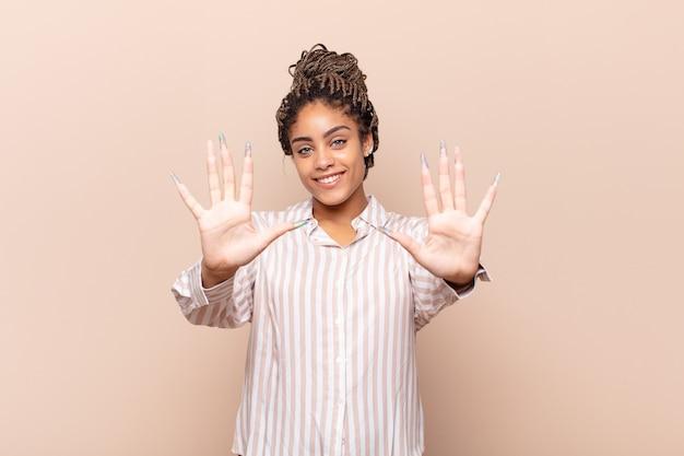 Młoda kobieta afro uśmiechnięta i wyglądająca przyjaźnie, pokazująca liczbę dziesięć lub dziesiątą ręką do przodu, odliczając w dół