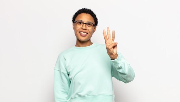 Młoda kobieta afro uśmiechnięta i wyglądająca przyjaźnie, pokazująca numer trzy lub trzeci z ręką do przodu, odliczający