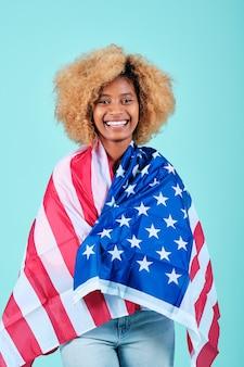 Młoda kobieta afro uśmiechnięta, owinięta flagą usa na odosobnionym tle. koncepcja obchodów dnia niepodległości i patriotyzmu.