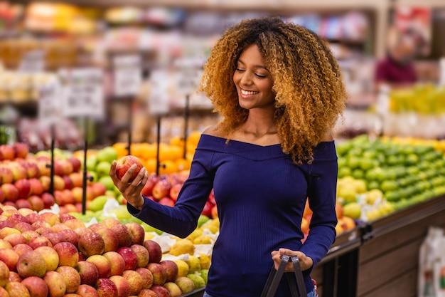 Młoda kobieta afro w supermarkecie kupuje jabłka.