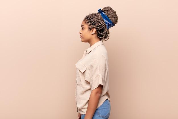 Młoda kobieta afro w widoku profilu chce skopiować przestrzeń do przodu, myśląc, wyobrażając sobie lub marząc