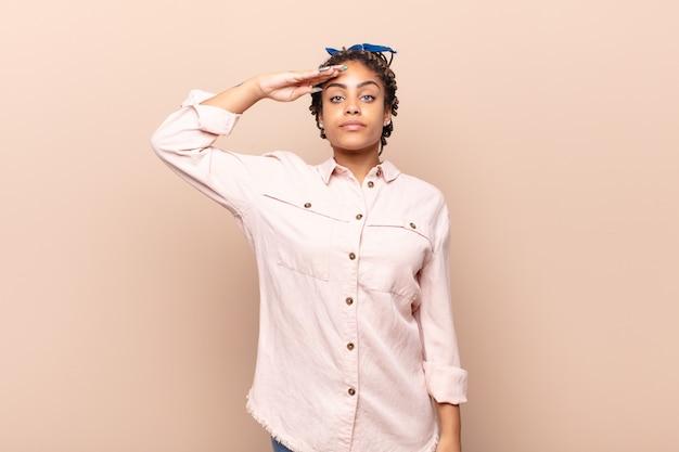 Młoda kobieta afro wita aparat z wojskowym salutem w akcie honorowym na białym tle