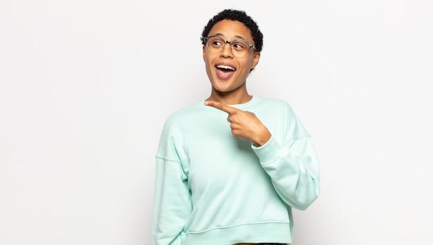 Młoda kobieta afro wygląda na podekscytowaną i zaskoczoną, wskazując na bok i w górę, aby skopiować przestrzeń