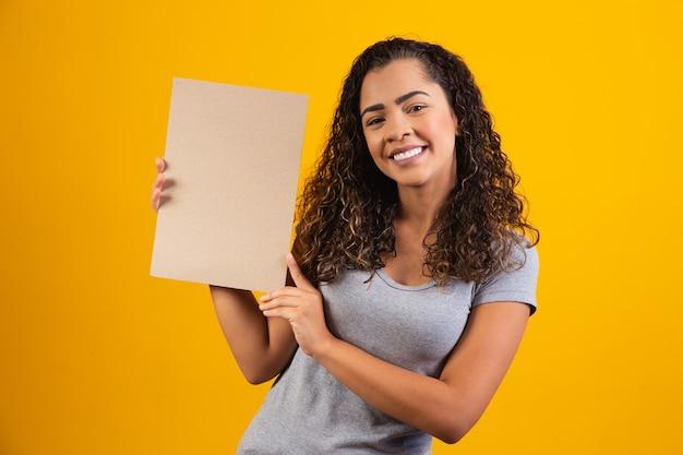Młoda kobieta afro z kartą z wolnego miejsca na tekst. koncepcja promocji. oferta. czarny piątek