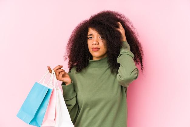 Młoda kobieta afro zakupy na białym tle młoda kobieta afro kupująca isolamłoda kobieta afro trzymająca róże na białym tle jest zszokowana, przypomniała sobie ważne spotkanie. <mixto>