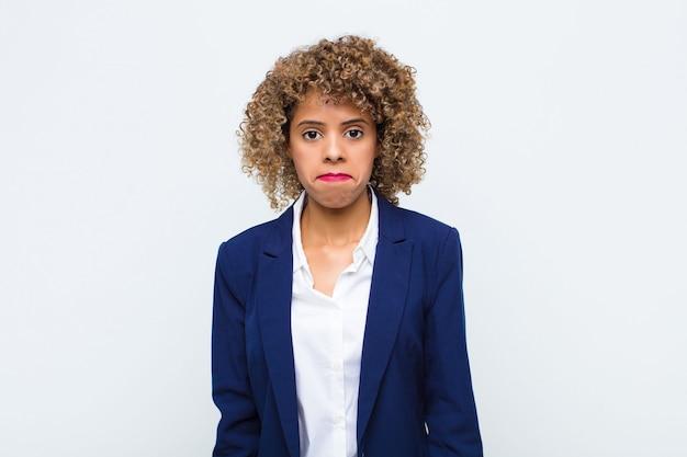 Młoda kobieta, afroamerykanin, czuje się smutna i zestresowana, zdenerwowana z powodu złej niespodzianki, z negatywnym, niespokojnym spojrzeniem na płaską ścianę