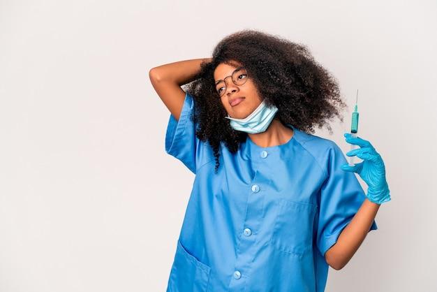 Młoda kobieta afroamerykanin kręcone lekarz trzymając strzykawkę dotykając tył głowy, myśląc i dokonując wyboru.